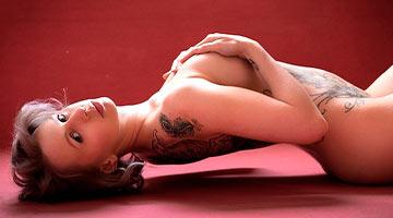 Tara Trouble liegt nackt auf dem Boden, mit ihren Händen bedeckt sie ihre Brüste